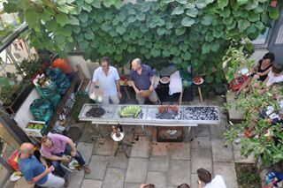 Tenth anniversary party: view from unit 4 down into front courtyard and food being grilled