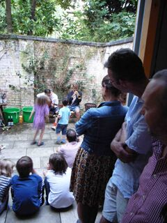 Tenth anniversary party: view from unit 3 into rear courtyard of Theo playing guitar, Gabriel playing trumpet, Freda and Luca dancing