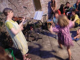 Tenth anniversary party: view of rear courtyard with Nicolette playing violin accompanied by Freda and Luca dancing