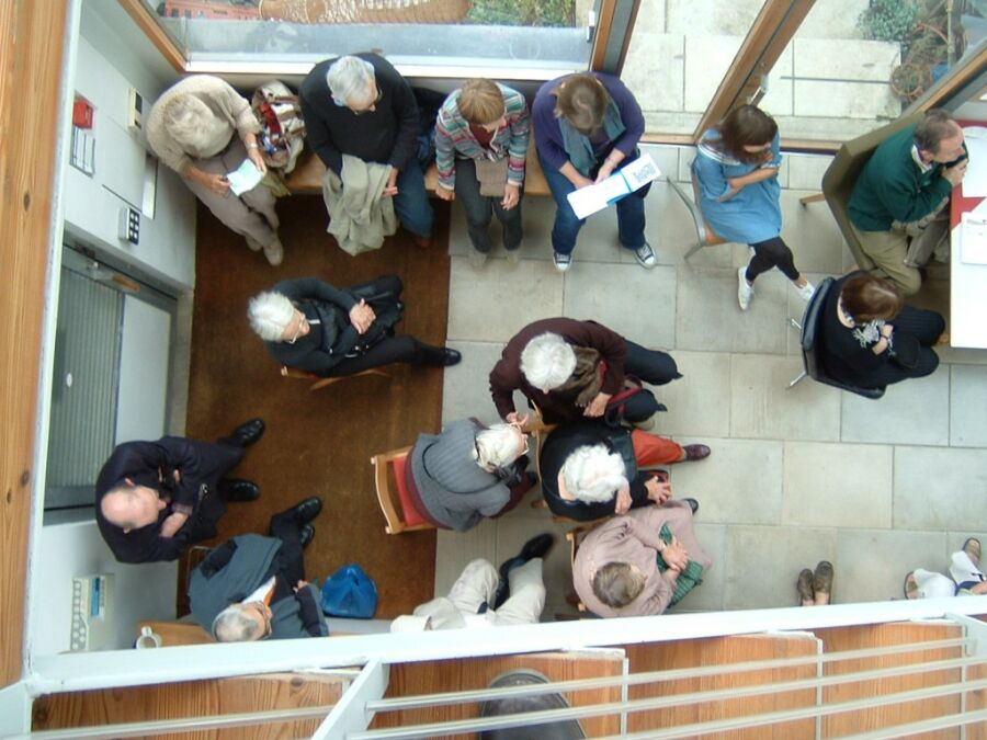 Gathering of audience members viewed from above in atrium for recital